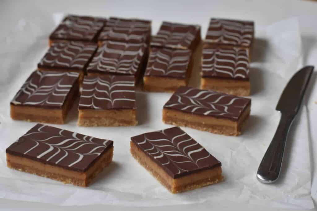 Caramel slice pieces on baking paper.