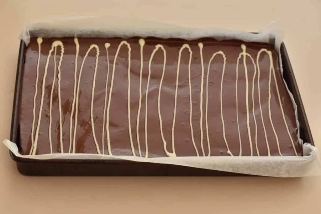 White lines piped on top of the dark chocolate topping.