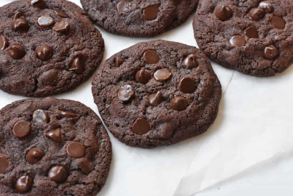 Double chocolate chip cookies on baking paper.