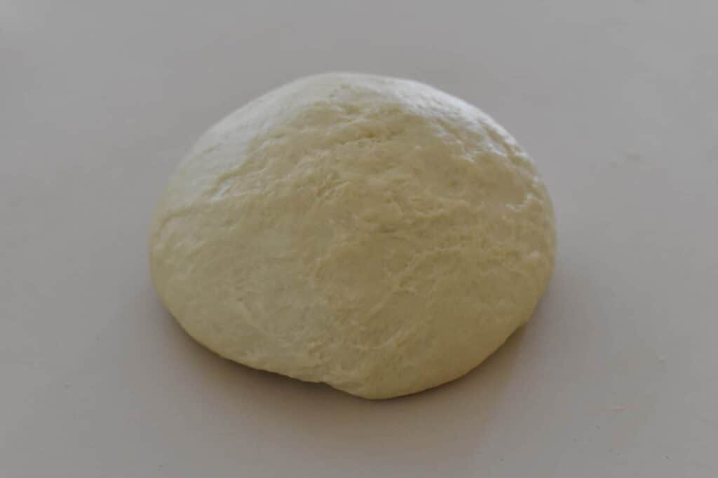 Kneaded smooth dough ball sitting on bench.