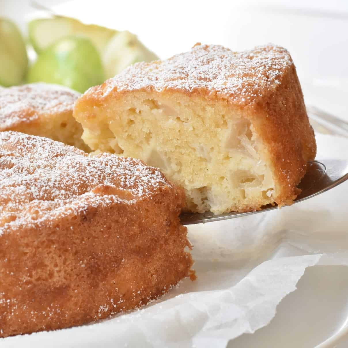 French Apple Cake slice being lifted from plate.