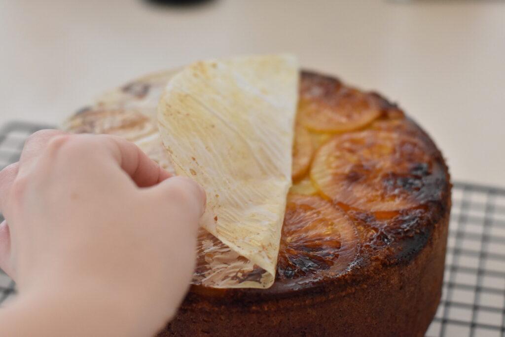 Baking paper being peeled off base of hazelnut cake.