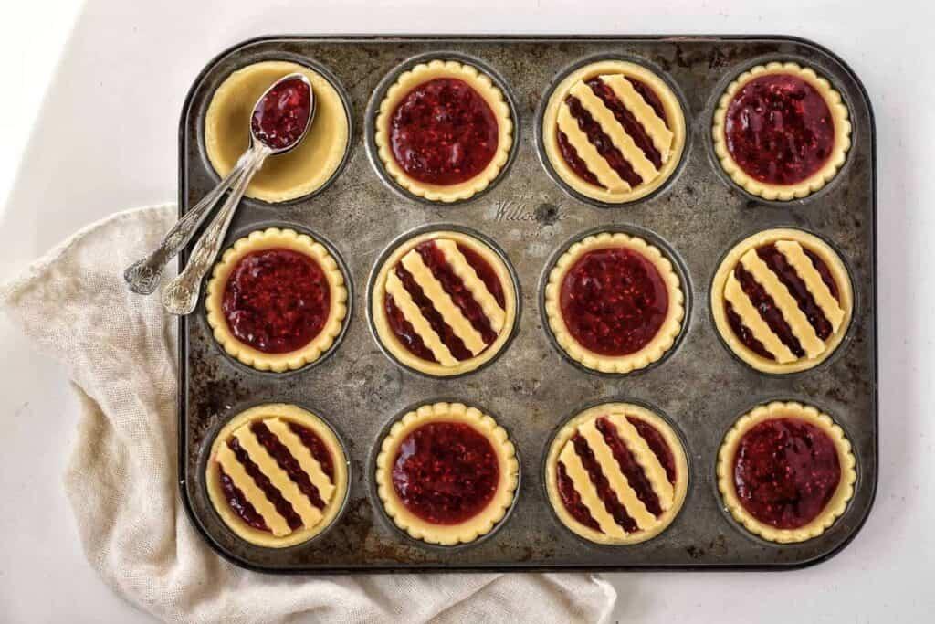 Jam tarts in tray before baking.