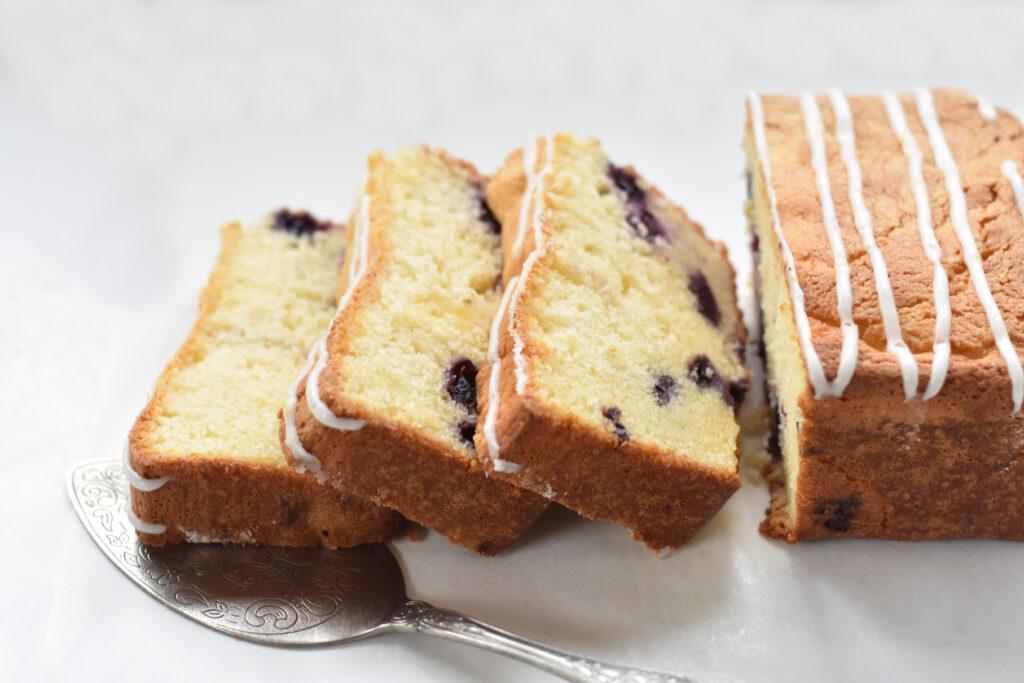 Slices on blueberry pound cake on cake server.