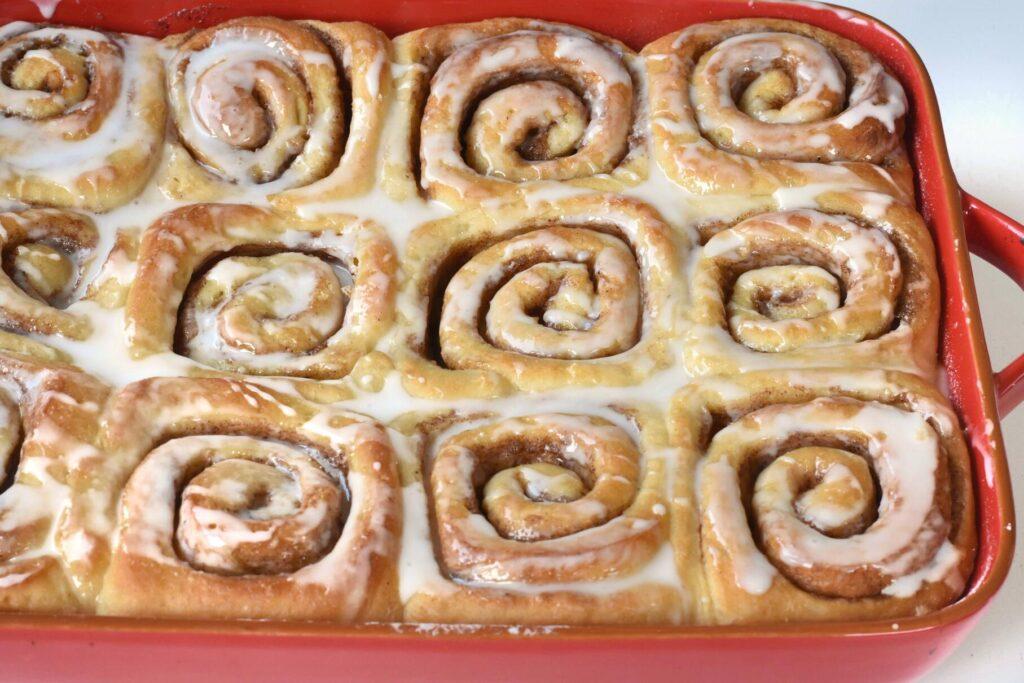 Glazed cinnamon rolls in tray.