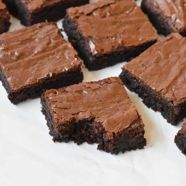 Squares of brownie cut up on baking paper.