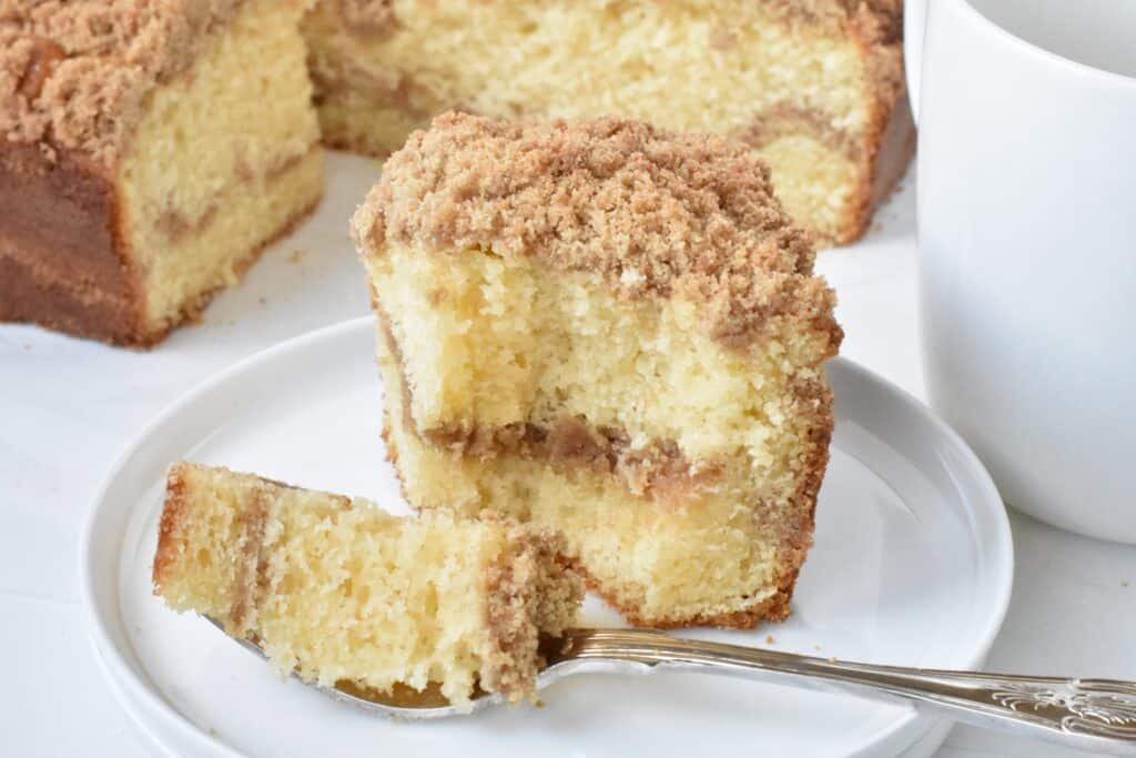 Slice of coffee cake on plate with fork and cup.