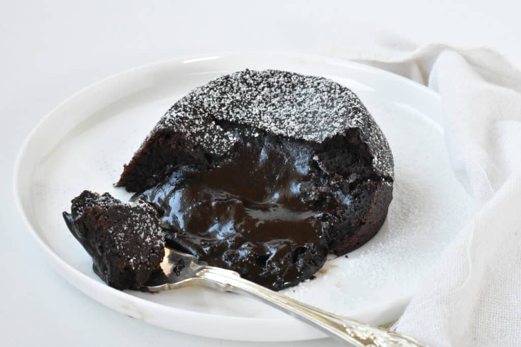Molten lava cake on plate with forkful.