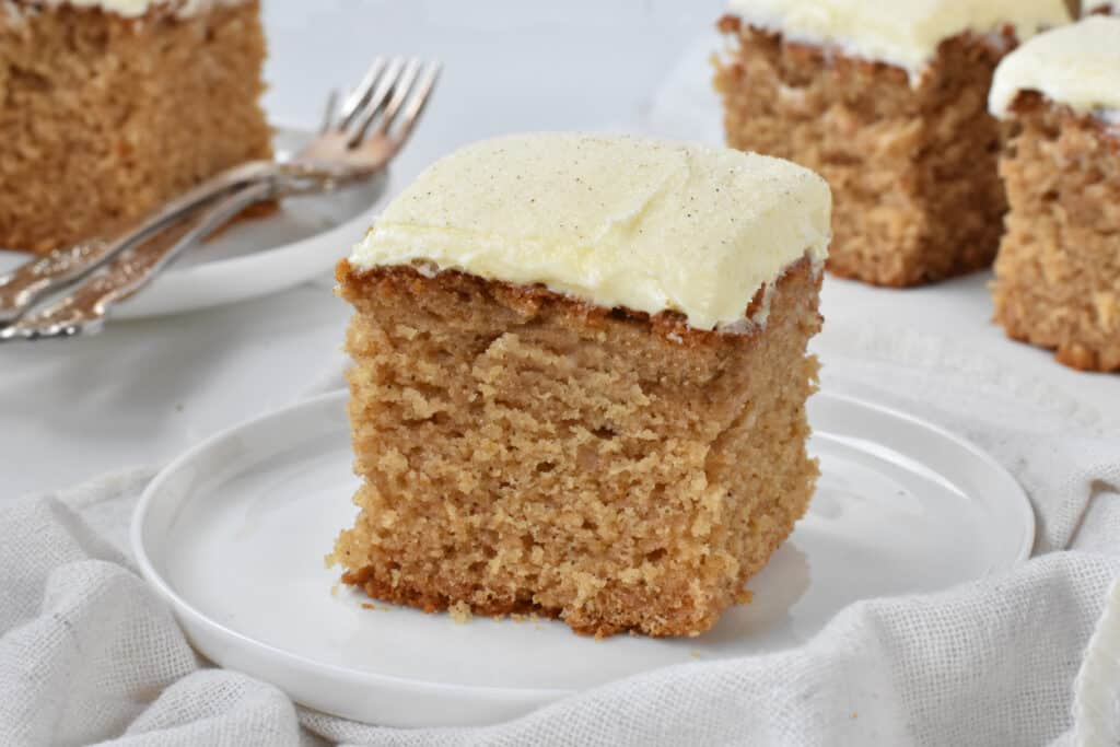 Square of spice cake with frosting on a plate.