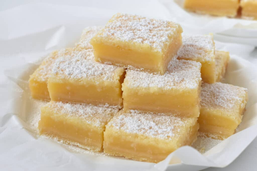 Lemon Coconut Bars stacked on a plate.