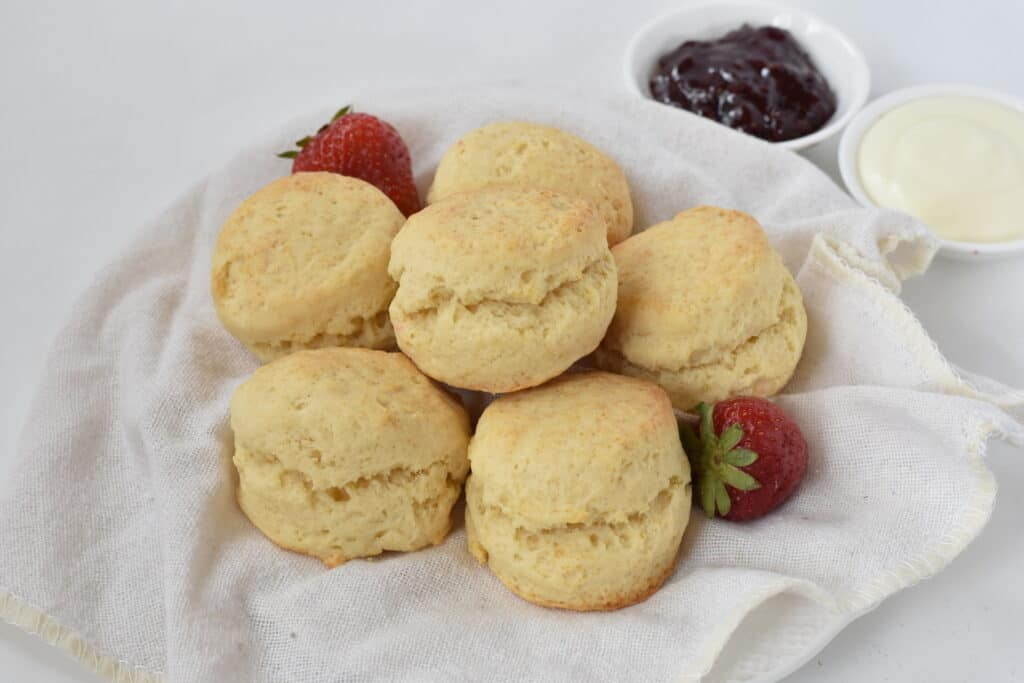 Scones stacked up on a plate with jam.