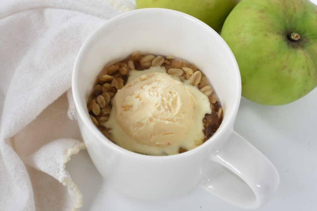 Apple crisp in mug with ice cream.