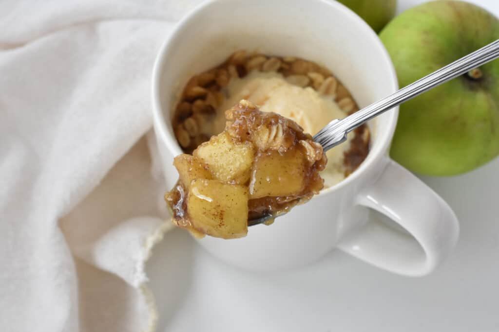 Apple crisp in mug with ice cream and close up of spoonful.